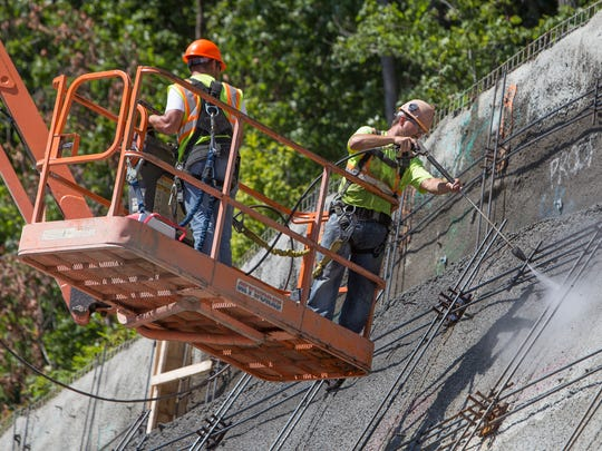 Workers power wash the retaining wall along Route 17 West on Aug. 17.