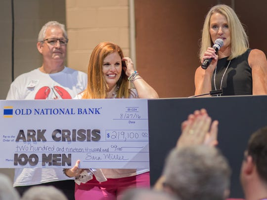 Angie Richards Cooley (center) of Ark Crisis Care Center accepts an oversized check from Old National Bank's Bob Jones (left) and Sara Miller (right) at the 100 Men Who Cook fundraiser. The final total wound up to be $221,000.
