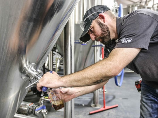Centerpoint Brewing co-founder Jonathan Robinson takes measurements from one of the tanks.