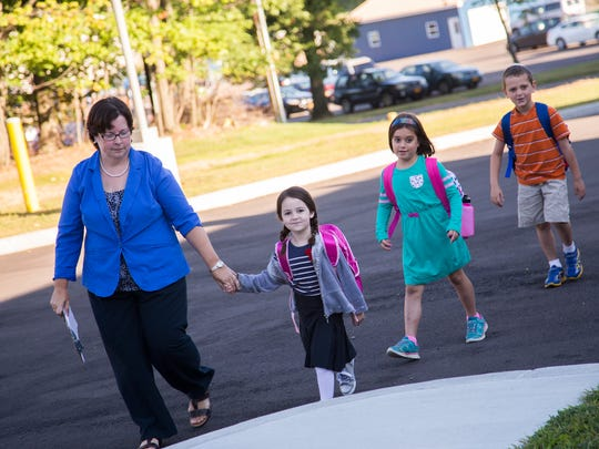 Principal Wendy Stafford leads students off the bus on the first day of school at Temple Israel in Vestal.