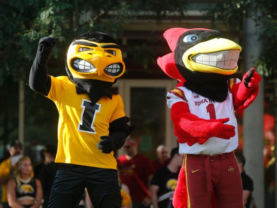 Herky and Cy applaud event organizers during the Rivalry