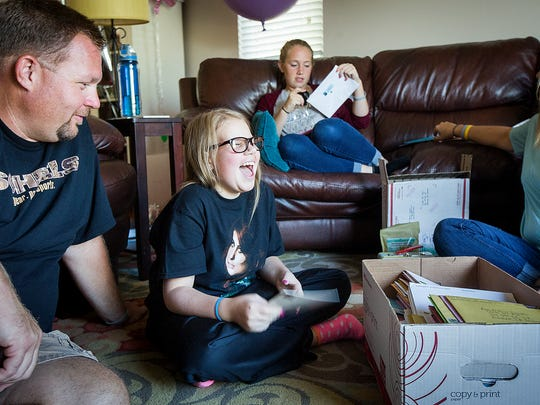Ava Hutchinson laughs while opening birthday cards with her dad Kris, sister Emma, 14, and mom Joni, at their home in Bondurant, Monday, Sept. 12, 2016. After deciding she didn't want gifts, only cards with donations for the Children's Cancer Connection, people from around the world have sent words of kindness and encouragement. Her parents can't even begin to estimate how many cards they have received.