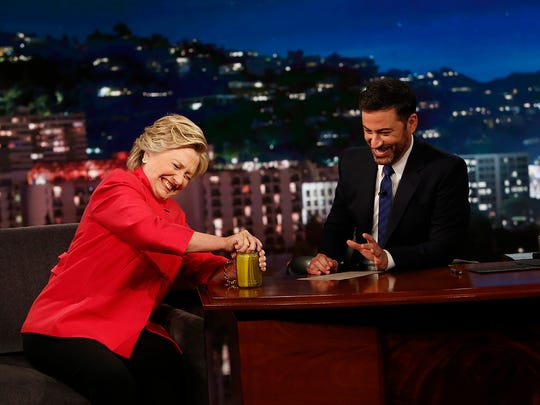 Presidential nominee Hillary Clinton opens a jar of pickles as Jimmy Kimmel watches during his ABC late-night show.