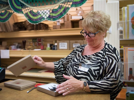 Sandra Gochnauer, a volunteer at Ten Thousand Villages in Greenville, gift wraps an item for a customer on Friday, September 16, 2016.