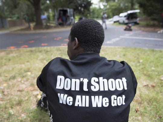 Dino Davis sits at the location where Keith Scott was shot by police in Charlotte on Wednesday, September 21, 2016.