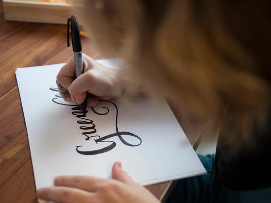 "Whitney Barnard, creative director of The Scribble Studio, hand letters ""Greenville"" in her home on Tuesday, September 20, 2016."