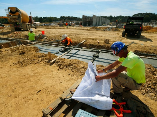A construction worker looks over plans as a footing