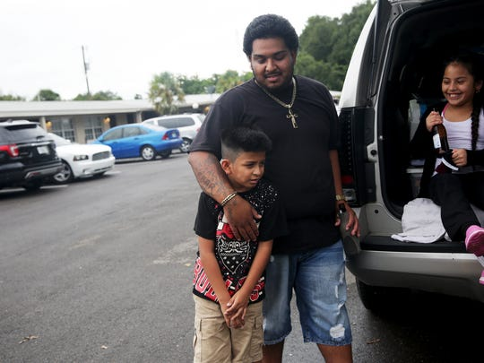 Cesar Zamora of Belle Glade holds his son Cesar III, 8, while grilling out with family outside of their hotel rooms at Motel 82 in Immokalee on Thursday, Oct. 6, 2016. The group evacuated from Belle Glade in Palm Beach County and traveled to Immokalee to wait out Hurricane Matthew.