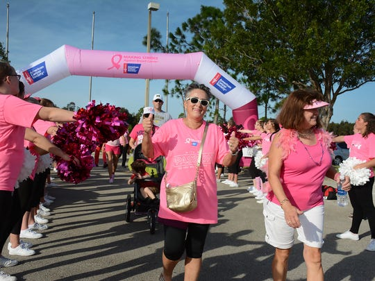 "Marchers celebrate finishing the walk with the help of the North Fort Myers High School cheerleaders. Thousands walked around and through Miromar Outlets in Estero Saturday morning for ""Making Strides Against Breast Cancer,"" raising funds to fund cancer research."