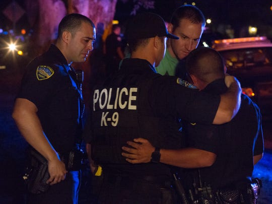 Officers comfort each other after the bodies of two