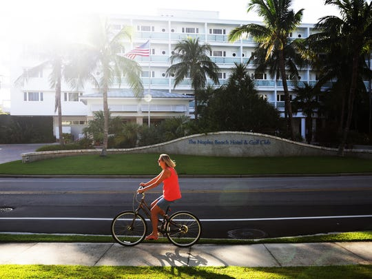 A woman rides her bicycle outside the Naples Beach Hotel & Golf Club on Monday, Oct. 10, 2016. The Watkins family is looking into selling the hotel after 70 years of operating it.