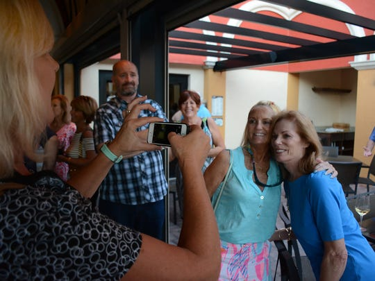 Cs & Qs - Mary Quinton snaps a photo of Chris, right, with Kathy Quinlan. Friends of Don Farmer and Chris Curle, longtime broadcast journalists and Marco residents who are moving off the island, gathered at Marco Prime Monday evening to have a drink or two and wish them well.