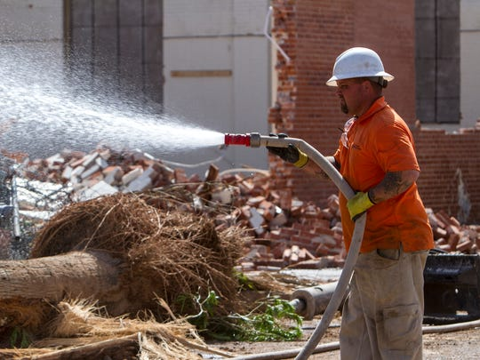 A demolition worker sprays water on debris at the historic Circles building after part of it was demolished on Friday, Apr. 15, 2016 in Phoenix. The building was once home to an auto-dealership and a records store.