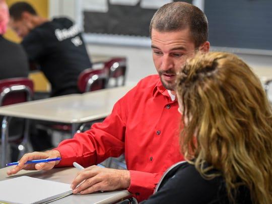 Academy for Innovative Studies teacher David Steckel helps Kira Almon in geometry class.
