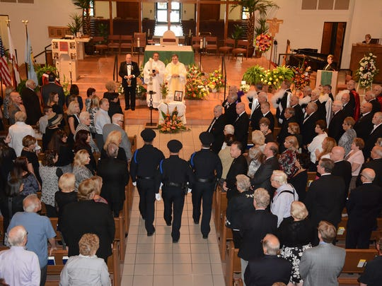 A Marco Island Police Dept. honor guard retrieves the Colors at the end of the service. Hundreds gathered at San Marco Catholic Church on Wednesday morning for a memorial service honoring the life of island stalwart Dick Shanahan.