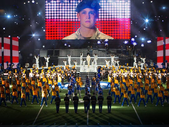 Billy Lynn (Joe Alwyn, on video screen) is saluted