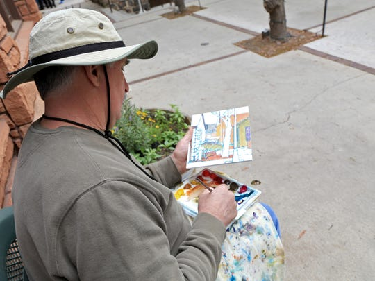 Royden Card paints at Ancestor Square in St. George in 2014.