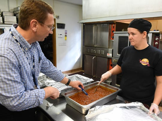 Vanderburgh County Health Department restaurant inspector Chris Borowiecki checks the temperature of a pan of food that Bauerhaus employee Lynda Jones just pulled from a oven Monday, October 31, 2016.