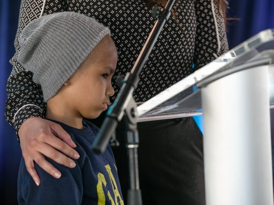 Bradley Becerra stands on stage as his mother, Bibiana
