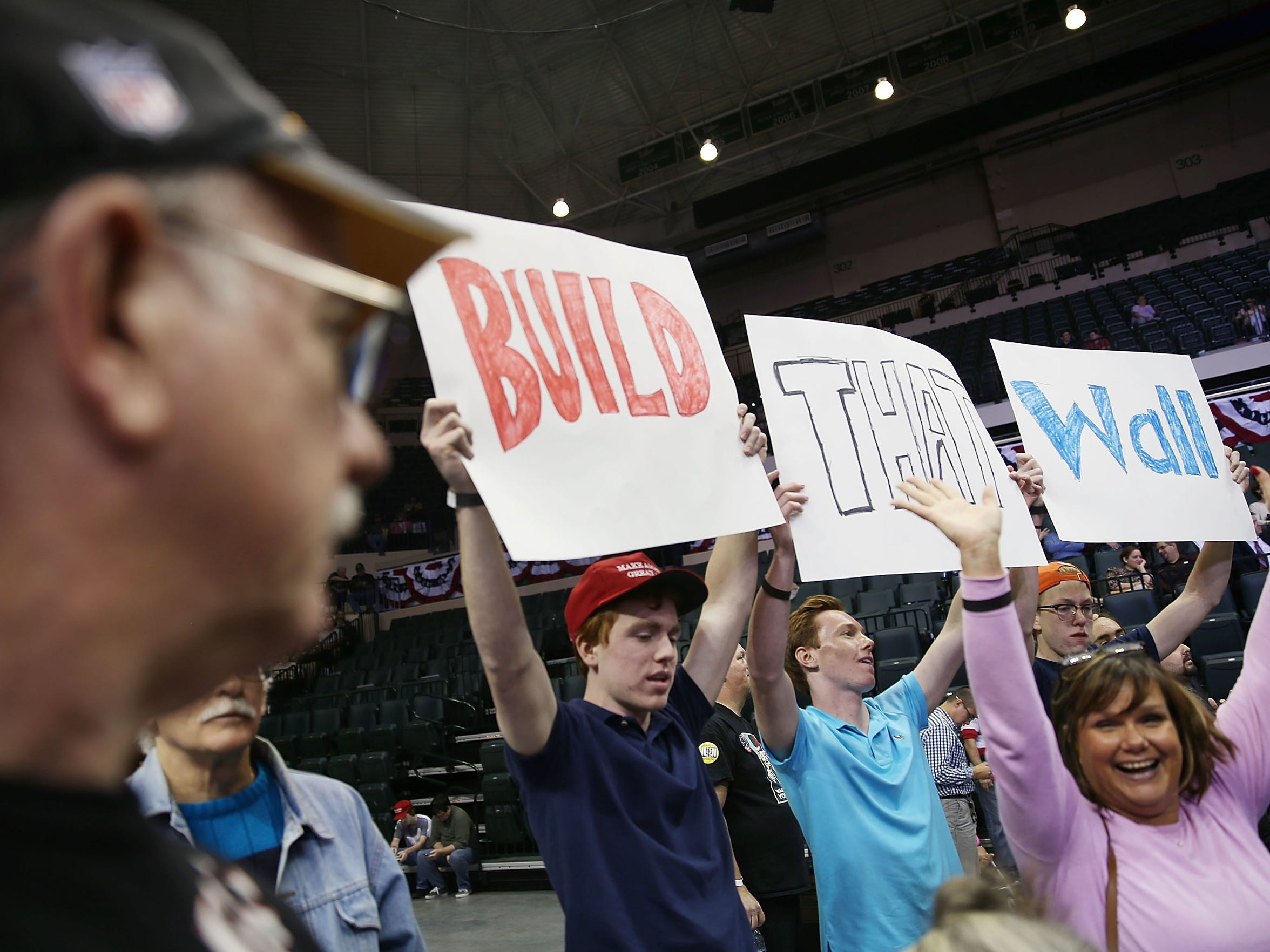 """People hold signs that read """"Build that Wall"""" as they wait the start of a campaign rally for Donald Trump on Feb. 12, 2016, in Tampa, Fla."""