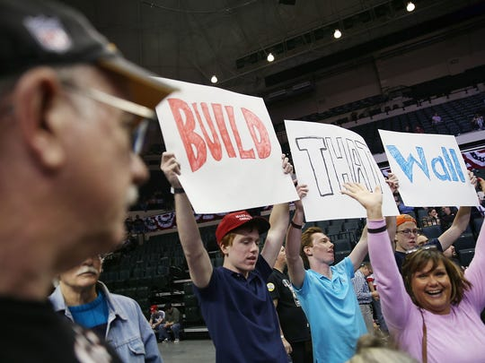 "People hold signs that read ""Build that Wall"" as they wait the start of a campaign rally for Donald Trump on Feb. 12, 2016, in Tampa, Fla."