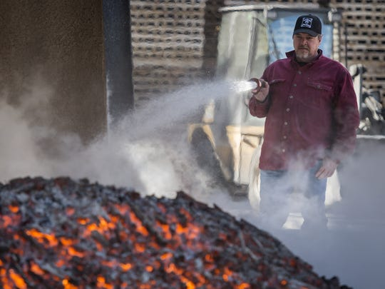 A Jack Daniel's worker sprays water to cool down charcoal, which will be used to filter the Tennessee whiskey at the historic Lynchburg, Tenn. distillery. The company violated its water quality permit in 2017, but has since come back into compliance.