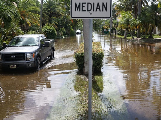 A vehicle drives through flooded streets  caused by the combination of the lunar orbit which caused seasonal high tides and what many believe is the rising sea levels due to climate change on September 30, 2015 in Fort Lauderdale, Florida.  South Florida is projected to continue to feel the effects of climate change and many of the cities have begun programs such as installing pumps or building up sea walls to try and combat the rising oceans.