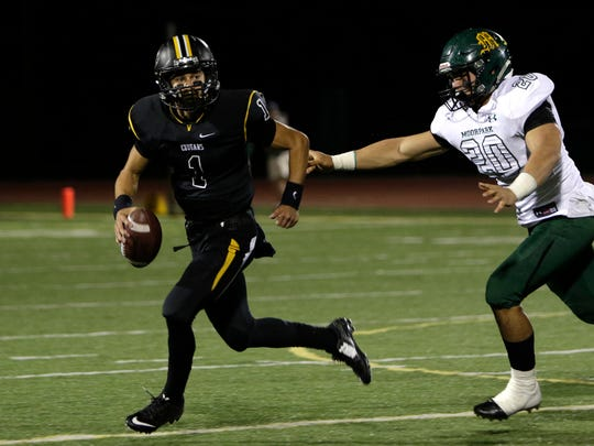 Ventura High quarterback Jack Gutierrez runs away from Moorpark's Nacho Robles during Friday night's Division 5 first-round playoff game at Ventura.