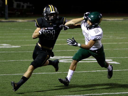 Ventura's Broc Mortensen stiff-arms Moorpark's Cameron Feaster during Friday night's playoff game in Ventura.