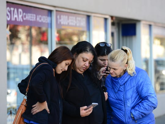 From left, Astrid Salas, 21 of Passaic, Daisy Rouse, 44, of Passaic, Denia Pena, 21, of Passaic, and Milinka Djurich, 56, of Clifton, gather around a smartphone to get more information about the school's closing. Star Career Academy gave little notice to its students that the school would be closing Wednesday. Students found out Tuesday night that school was closing leaving them in the middle of their schooling without a diploma.