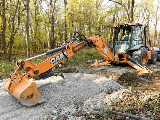Henderson County Road Department worker Mike Rideout uses a backhoe to fill a low spot as crews build a handicapped accessible trail to the Audubon State Park wetlands boardwalk Tuesday, November 15, 2016.