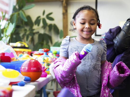 Jayonna Randall, 8, checks out a toy microphone at New Life Toys in the People's Ministry in Christ building on Dewey Avenue in 2015.