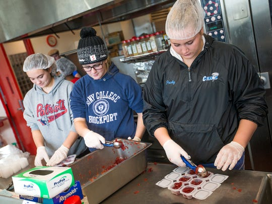 Binghamton High School students, from right, Mikayla Pourby, 16, Emily Saunders, 17, and Madison Hodges, 17, prepare cranberry sauce sides for the 21st annual Thanksgiving meal on Wednesday, Nov. 23. The dinner, which is free to the public, will run from 11:30 a.m. to 2 p.m..
