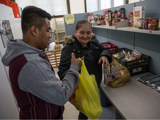 Adan Pacheco, an employee of the charity, helps Blanca