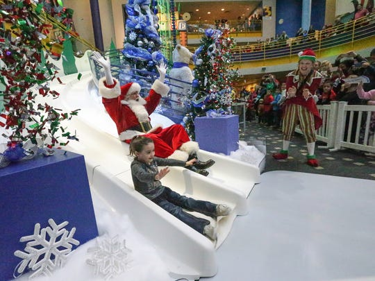 Indianapolis Children's Museum member Lauren Brassard slides down the Yule Slide with Santa during a Jolly Days celebration, Friday, Nov. 25, 2016.