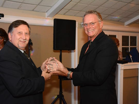 Chamber president Alex Parker III, right, congratulates Philip Penzo of Marco Office Supply on winning the President's Recognition Award. The Marco Island Area Chamber of Commerce held its annual Christmas Gala Sunday at Bistro Soleil, announcing winners for the Citizen of the Year, Volunteer of the Year, and President's Recognition Award.