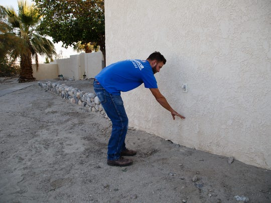 Jonny Malette points to the level that water reached on the side of his family's Thousand Palms home during a flood in 2014, Monday, December 5, 2016.