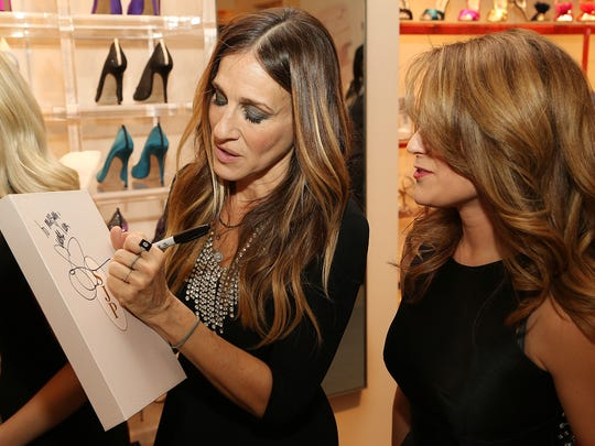 Sarah Jessica Parker signs an autograph for a shopper