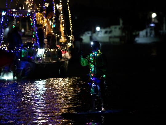 A paddle boarder is seen wearing Christmas lights during the 51st annual Parade of Lights held at Channel Island Harbor Saturday evening.