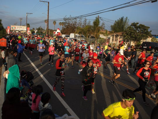 People run along Ventura Boulevard during the ninth annual Santa to the Sea half-marathon.