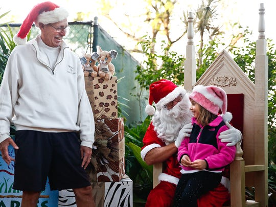 Rich Manietta laughs along with his granddaughter Lucie Manietta, 6, as she tells Santa what she wants for Christmas during the Naples Zoo's Tropical Santa event on Sunday, December 20, 2015.