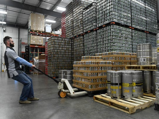 Jason Hoffman, Tin Man Brewing Company operations manager, moves a pallet of canned beer at their West Franklin facility Saturday. The brewer ships more than 1,000 cases a week, December 17, 2016.