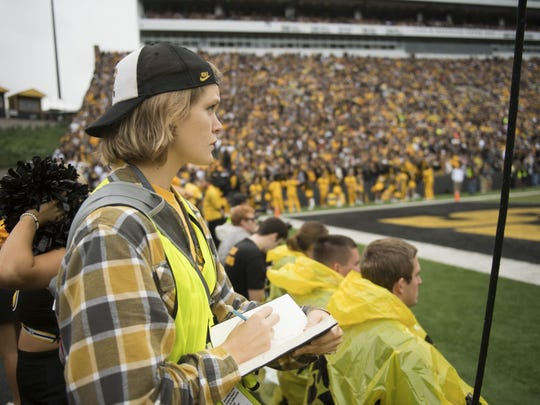 Elinor Krieger-Coble, a regent graduate in the UI School of Art and Art History, sketches from the sidelines of Kinnick Stadium during Iowa football games.