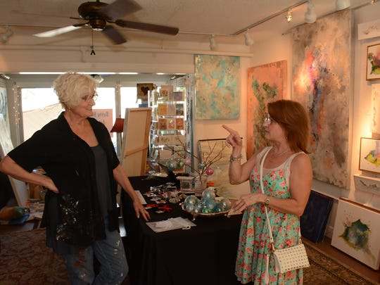 "Lynn Knickerbocker, right, talks with artist Betty Newman about her work. A group of Marco Island artists have joined together in gallery spaces at the Shops of Old Marco, creating an artists' colony and offering ""the gift of art"" in a wide price range."