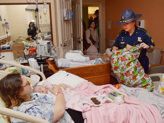 La. State Trooper Amanda Fournier (right) visits one-month-old Renesmee Chapman and her mother Jennifer Chapman at Rapides Womens and Childrens Hospital Christmas Eve morning. Members of Troop E along with family members visited area hospitals to hand out gifts to children in the hospital. Chapman said that unfortunately Renesmee will have to spend her first Christmas in the hospital. She has six other siblings at home.