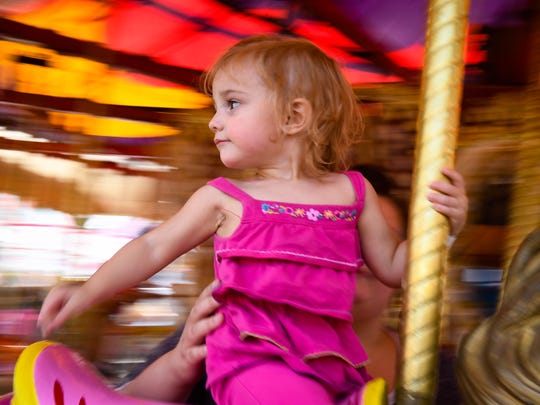 I love the dream-like quality in this picture of two-year-old Symphony Stout shot at the Evansville Fall Festival. I used a slow shutter speed and panned the movement of the merry-go-round to capture the color and movement around her. After dozenÕs of failures, this single frame had the qualities I was looking for.