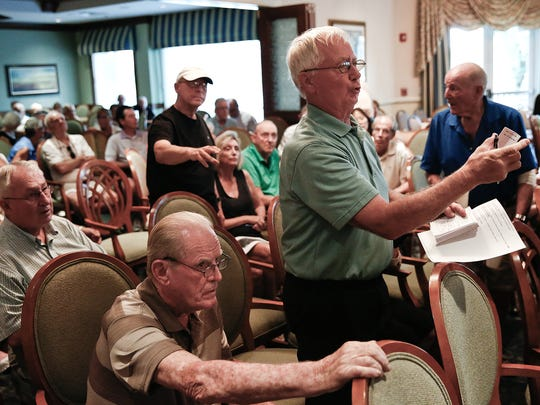 Lyle Odland, right, asks about when the Lee County School Board meets during a crowded public forum at Worthington Country Club on Monday, Nov. 2, 2015 about a proposed site for a high school near the Hunters Ridge, Worthington and Quail West communities in Bonita Springs. Residents of those communities raised several concerns about how the proposed school location could affect them. (Scott McIntyre/Staff)