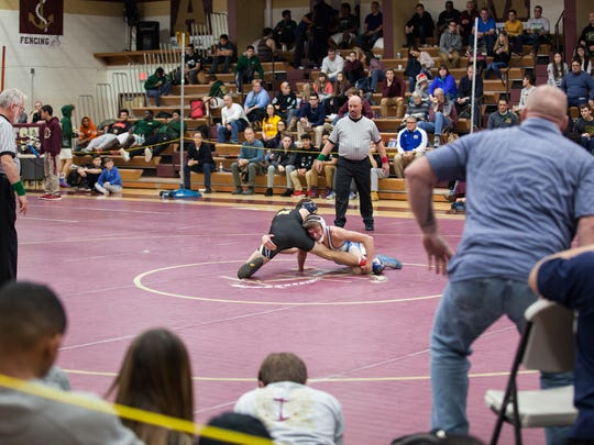 John Jay wrestling coach Jamie Weaver looks on as Randy Earl and Jack Bokina of Mattituck face off for the 126 pound title at the 51st Annual Mid-Hudson Wrestling Invitational at Arlington High School December 28, 2016.