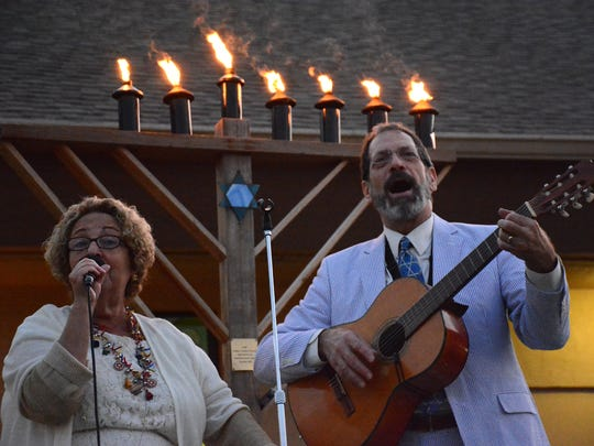 Cantor Hari Jacobsen leads the singing, accompanied by Rabbi Mark Gross on guitar. The Jewish Congregation of Marco Island held a Hanukkah celebration on Thursday evening outside the temple on Winterberry Drive.