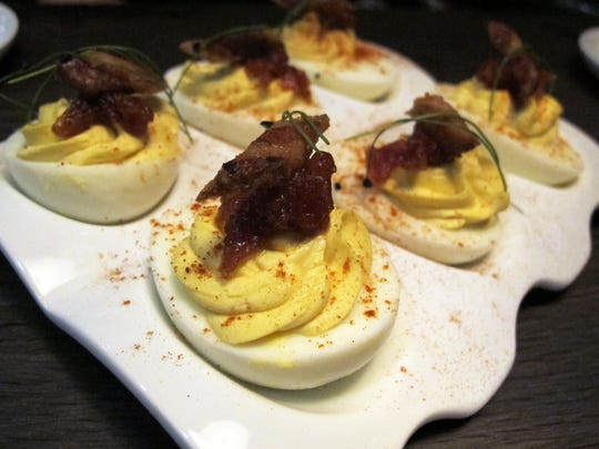 The bacon and eggs appetizer at Public House features deviled eggs with tomato jam and candied bacon.